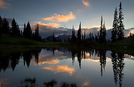Mount Rainier is silhouetted above the clouds during a sunset at Upper Tipsoo Lake in Mount Rainier National Park, Washington State, USA