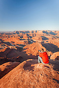 Tourist photographing at Dead Horse Point, Arches National Park, Utah, United States of America