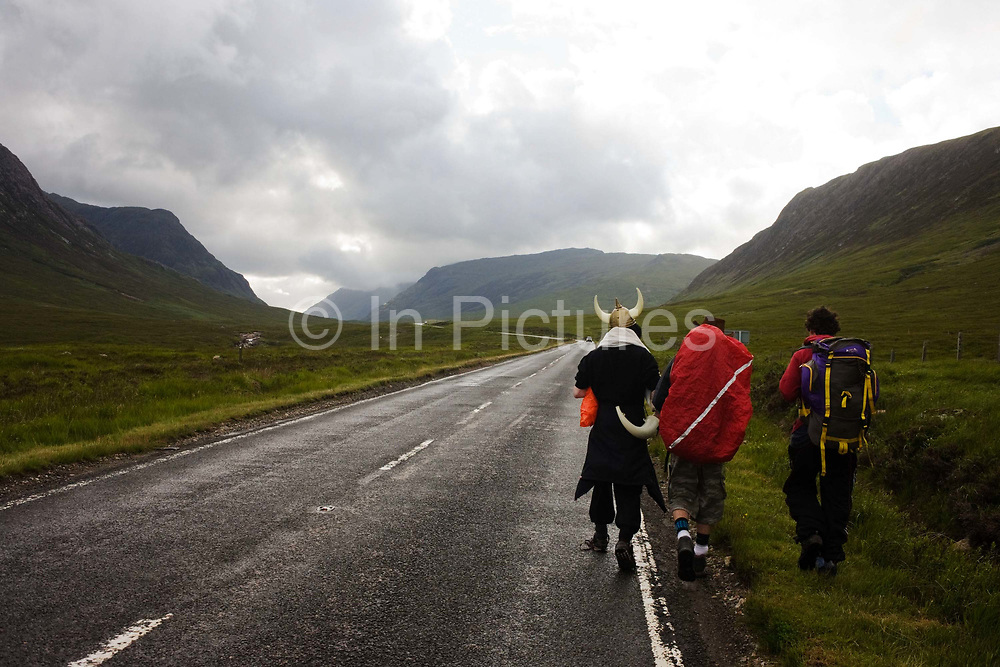 Wearing a plastic Viking horn helmet, one of three friends make their way along a high-altitude deserted road amid the spectacular wilderness of Glencoe, a valley surrounded by high peaks 3,000 feet (1,000m) high mountains. The landscape is magnificent but unforgiving and walkers mainly stay on well-marked paths or, as these lads are doing - walking along the A82 road that snakes through this Scottish Glen. They admit to having trekked from Glasgow on pagan fertility Wassail rite, once performed in medieval times. This region of Britain, lake many others, was populated by Viking raiders who later settled locally and raised families whose descendents now inhabit the UK. English is full of old Norse words as are place names.