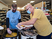 "26 APRIL 2020 - JEWELL, IOWA: KENN OUTZEN and DEAN KOOB, members of the group trying to reopen a grocery store in Jewell, plate up roast pork dinners for grab and go meals during a fund raiser Sunday. Jewell, a small community in central Iowa, became a food desert when the only grocery store in town closed in 2019. It served four communities within a 20 mile radius of Jewell. Some of the town's residents are trying to reopen the store, they are selling shares to form a co-op, and they hold regular fund raisers. Sunday, they served 550 ""grab and go"" pork roast dinners. They charged a free will donation for the dinners. Despite the state wide restriction on large gatherings because of the COVID-19 pandemic, the event drew hundreds of people, who stayed in their cars while volunteers wearing masks collected money and brought food out to them. Organizers say they've raised about $180,000 of their $225,000 goal and they hope to open the new grocery store before summer.PHOTO BY JACK KURTZ"