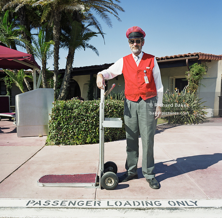 A gentleman Sky Cap stands in front of the terminal building at Santa Barbara Municipal Airport, California, USA. Wearing his red waste-coat, ID badge and cap he holds the handle of the baggage trolley with which he assists passengers to offload their belongings and guides them to the check-in counters inside. The man has a greying beard and sunglasses against the glare and is an eager helper to those struggling with heavy travel possessions. On the ground are stencilled the words 'Passenger Loading Only' referring to where departing travellers might seek help with baggage. There are armies of workers across the world keeping airlines and airports running 24/7. Picture from the 'Plane Pictures' project, a celebration of aviation aesthetics and flying culture, 100 years after the Wright brothers first 12 seconds/120 feet powered flight at Kitty Hawk,1903..