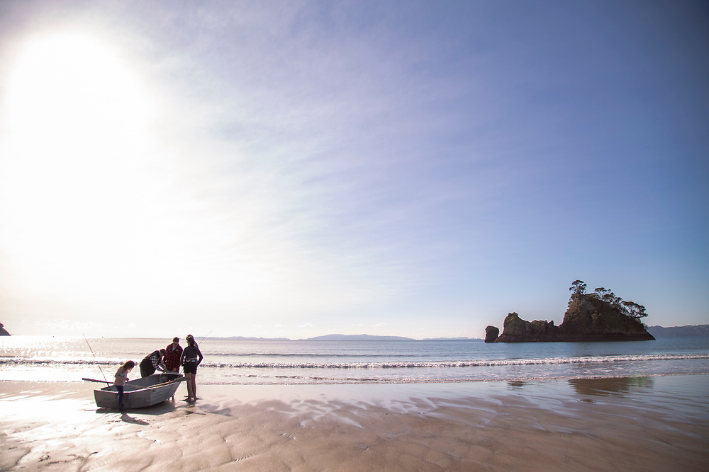 Family group preparing dinghy for fishing at Whangapoua Beach , East Coast, North Island