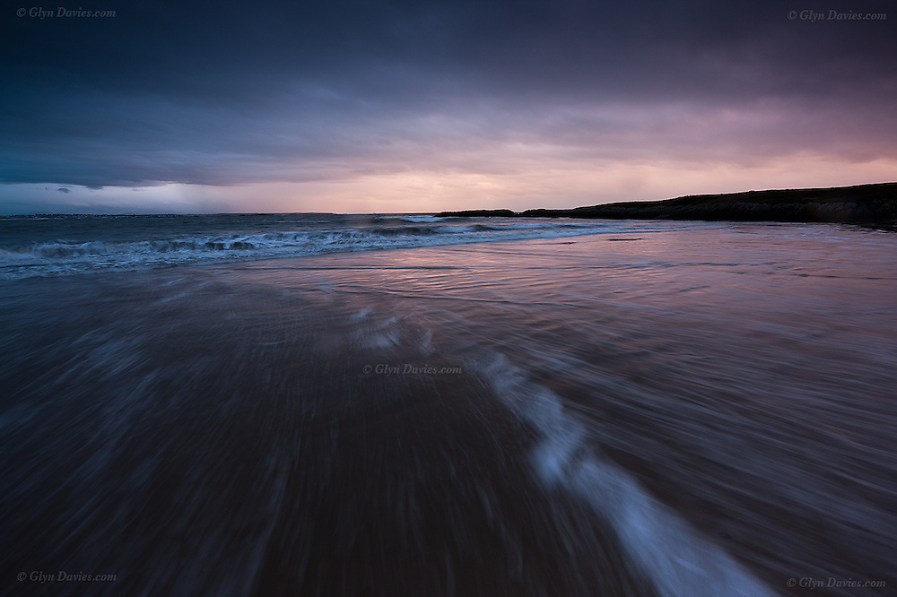 Subtle moments of brighter light at sunset after a wet, rainy day at Silver Bay, Anglesey. The advancing tide created a powerful backwash of waves.