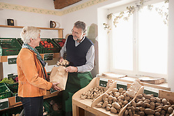 Mature woman buying potatoes in the store, Bavaria, Germany