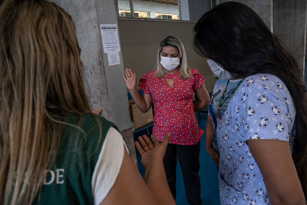 Nurses pray before administering the CoronaVac vaccine, also known as the Sinovac COVID-19 vaccine at Club Trabalhador/SESI in Manaus, Brazil March 30, 2021. CoronaVac is an inactivated virus COVID-19 vaccine developed by the Chinese company Sinovac Biotech and has been in Brazil's Phase III clinical trials. Photo Ken Cedeno