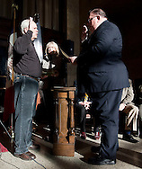 At Large Council Member Don Karr (left) repeats the oath of office with Pat Kane (right), diaconal minister with Crossroads Mission, as his wife, Patricia Karr (center) holds a bible at the Cedar Rapids mayor and city council swearing in ceremony at the Veterans Memorial Building in Cedar Rapids on Saturday January 2, 2010. (Stephen Mally/Freelance)