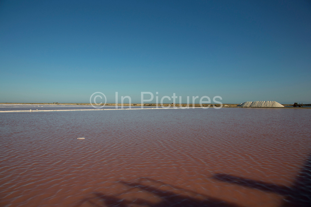 """Famous salt marshes at Gruissan, Languedoc-Roussillon, France. This area is very well known for producing sea salt from it's salt fields or marshes on this coastline. Sea salt farms, with giant hills of salt - """"Camelles"""", in differing shades of brown and white, and the flat """"fields"""" of salt water, in this case, turning pink."""