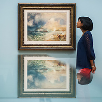London, UK - 8 September 2014: a gallery assistant poses next to 'Bamborough Castle c.1837' by J.M.W. Turner