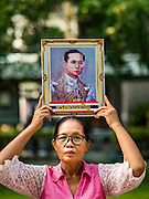 13 OCTOBER 2016 - BANGKOK, THAILAND:  A woman holds up portraits of Bhumibol Adulyadej, the King of Thailand, while she prays for him at Siriraj Hospital. Thousands of people came to the hospital to pray for the beloved monarch. Bhumibol Adulyadej, the King of Thailand, died at Siriraj Hospital in Bangkok Thursday, October 13, 2016. Bhumibol Adulyadej, 5 December 1927 – 13 October 2016, was the ninth monarch of Thailand from the Chakri Dynasty and is known as Rama IX. He became King on June 9, 1946 and served as King of Thailand for 70 years, 126 days. He was, at the time of his death, the world's longest-serving head of state and the longest-reigning monarch in Thai history.      PHOTO BY JACK KURTZ