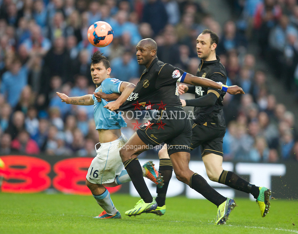 MANCHESTER, ENGLAND - Sunday, March 9, 2014: Manchester City's Sergio Aguero in action against Wigan Athletic's Emmerson Boyce during the FA Cup Quarter-Final match at the City of Manchester Stadium. (Pic by David Rawcliffe/Propaganda)