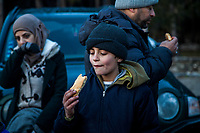 LESVOS, GREECE - FEBRUARY 09: A young boy eats a piece of bread given by volunteers after his arrival on a beach in South Lesvos with other refugees and migrants from the Turkish coast on February 09, 2015 in Lesvos, Greece. Photo: © Omar Havana. All Rights Are Reserved