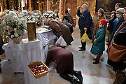 Moscow, Russia, 10/04/2004..Russian Orthodox Easter celebrations at the Church of Peter and Paul in central Moscow .One woman kisses an icon while another on her knees begs forgiveness. .
