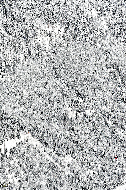 A lone red gondola glides above the upper reaches of the vast snow covered Whistler Mountain wilderness in British Columbia.