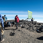 Climbers pose for photos next to the sign marking Uhuru Peak, the summit of Mt Kilimanjaro (19,341 feet).