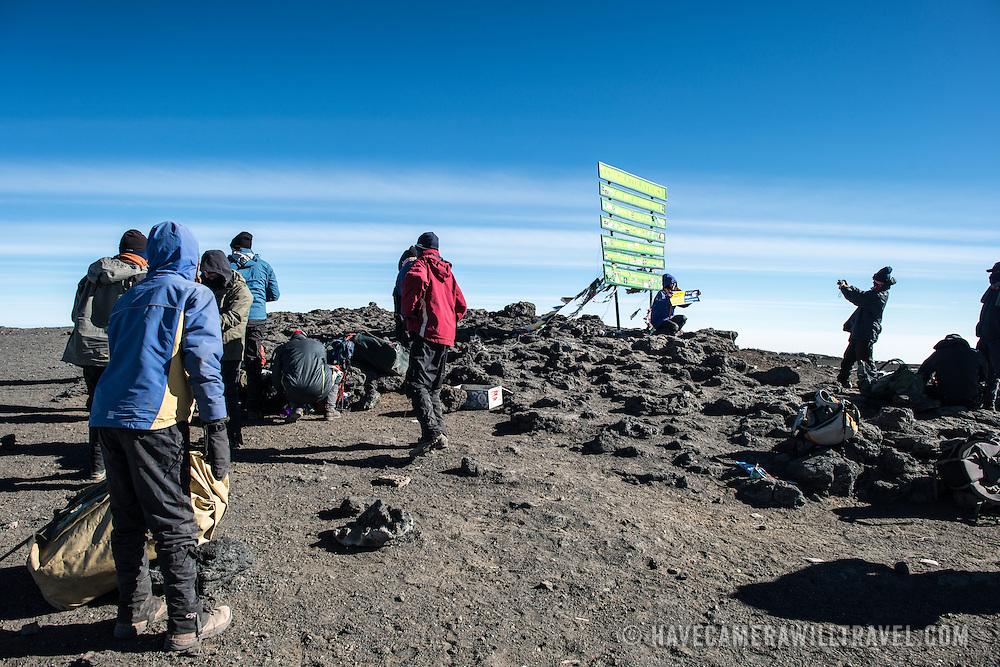 Climbers pose for photos next to the sign marking Uhuru Peak, the summit of Mt Kilimanjaro (19,341 feet).