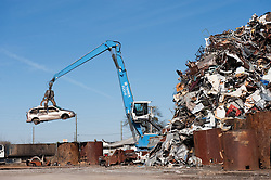 Crane lifting a mini-van into a pile of scrap metal for recycling