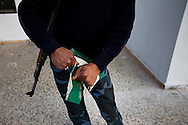 A rebel army volunteer rips up one of Qadaffi's green books in a town near Ras Lanuf  on March 3, 2011.