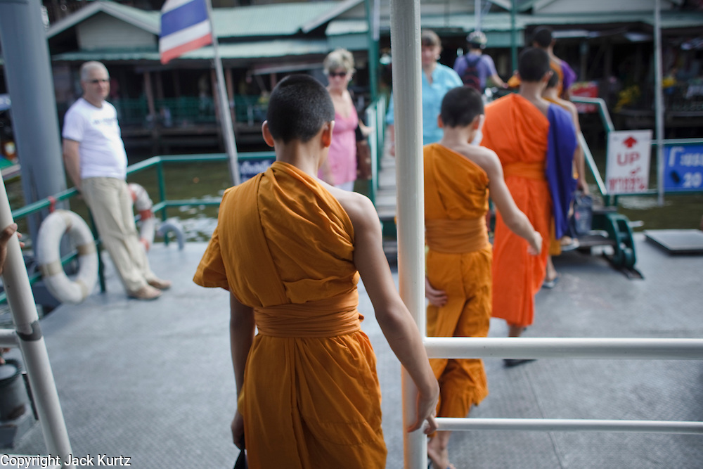 """Mar. 9, 2009 -- BANGKOK, THAILAND:  Young monks from Wat Arun get off a cross river ferry in Bangkok. Wat Arun is a Buddhist temple (wat) in the Bangkok Yai district of Bangkok, Thailand, on the west bank of the Chao Phraya River. The full name of the temple is Wat Arunratchawararam Ratchaworamahavihara. The outstanding feature of Wat Arun is its central prang (Khmer-style tower). It may be named """"Temple of the Dawn"""" because the first light of morning reflects off the surface of the temple with a pearly iridescence. Steep steps lead to the two terraces. The height is reported by different sources as between 66,80 m and 86 m. The corners are surrounded by 4 smaller satellite prangs. The prangs are decorated by seashells and bits of porcelain which had previously been used as ballast by boats coming to Bangkok from China. The central prang is topped with a seven-pronged trident, referred to by many sources as the """"trident of Shiva"""". Around the base of the prangs are various figures of ancient Chinese soldiers and animals. Over the second terrace are four statues of the Hindu god Indra riding on Erawan. The temple was built in the days of Thailand's ancient capital of Ayutthaya and originally known as Wat Makok (The Olive Temple). In the ensuing era when Thonburi was capital, King Taksin changed the name to Wat Chaeng. The later King Rama II. changed the name to Wat Arunratchatharam. He restored the temple and enlarged the central prang. The work was finished by King Rama III. King Rama IV gave the temple the present name Wat Arunratchawararam. As a sign of changing times, Wat Arun officially ordained its first westerner, an American, in 2005. The central prang symbolizes Mount Meru of the Indian cosmology. The satellite prangs are devoted to the wind god Phra Phai..Photo by Jack Kurtz / ZUMA Press"""