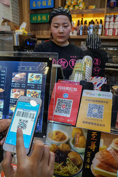 The process of scanning the QR code of the shop where you buy the items and the shop assistant scanning the code on your telephone to ascertain that you have bought the product
