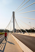 The Millennium Bridge is a cable stayed bridge that spans Moraca River with cables that form a graphic pattern and a single central supporting column. A young man walking on the bridge. Podgorica capital. Montenegro, Balkan, Europe. Designed by Mladen Ulicevic.