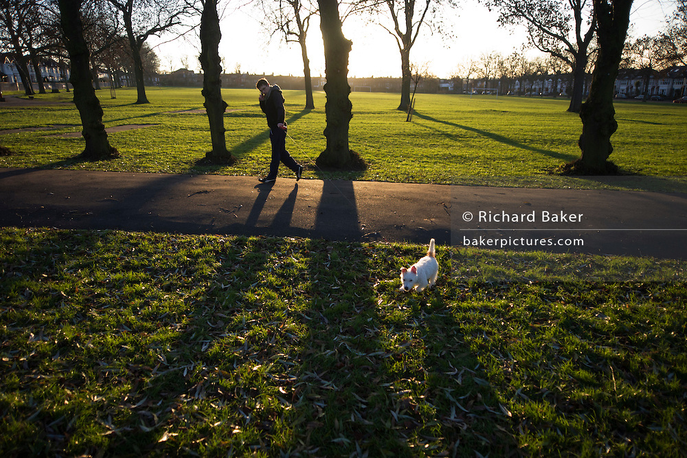 A dog owner walks his pet in a wide landscape of late winter light of south London's Ruskin Park.