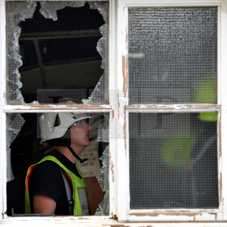© licensed to London News Pictures. MARLOW, UK.  03/08/11. A fireman seen through a broken window. Marlow Rowing Club has been badly damaged by fire today (03 August 2011). Boats with an estimated value of 100,000 pounds have been damaged. Steve Redgrave, Olympic Rower, who trained at the club and is from Marlow said his daughters boat is believed to be inside.  Mandatory Credit Stephen Simpson/LNP