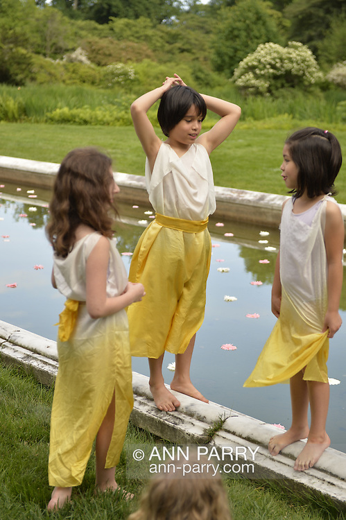 Old Westbury, New York, U.S. - June 21, 2014 - Nikolas Scheiber-Loeis and other members of Young Duncan Dancers, are at the Reflecting Pool with water lilies, before the start of Lori Belilove & The Isadora Duncan Dance Company dancing throughout the gardens during the Midsummer Night event at the Long Island Gold Coast estate of Old Westbury Gardens on the first day of summer, the summer solstice.