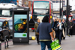 Modern public telephones carrying illuminated advertising add to the clutter of signs, lampposts, sandwich boards, bus shelters and street furniture on Edgeware Road in London. LONDON, February 12 2019.