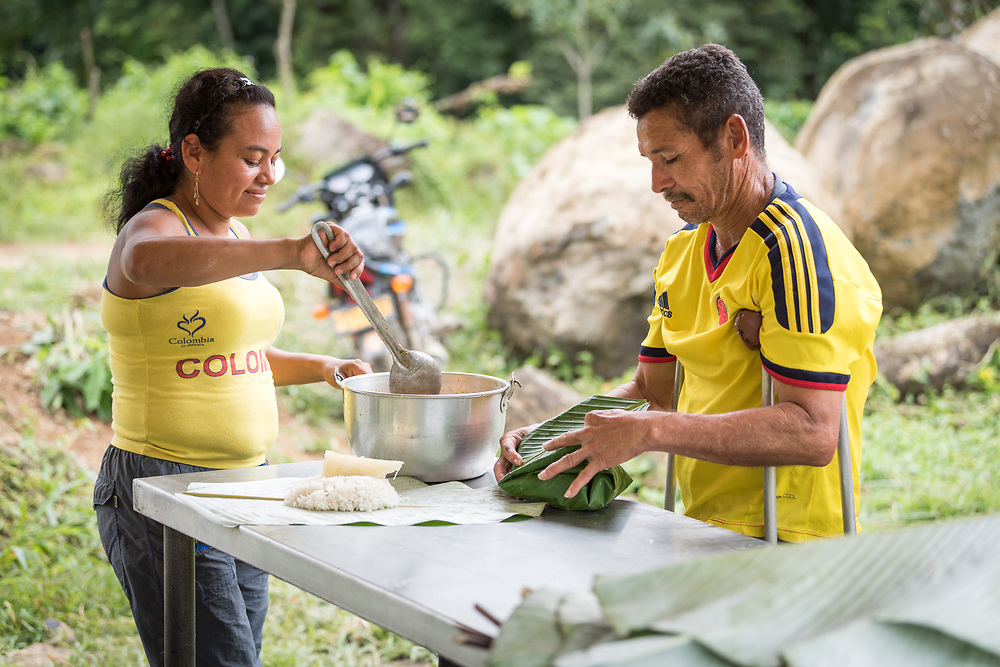 16 November 2018, San José de León, Mutatá, Antioquia, Colombia: Mayerlis serves 48-year-old Ivan a meal of sarapa – rice and chicken wrapped in a Cachibou leaf. Ivan walks on crutches as he is missing a leg. He lived 31 years as a FARC guerilla combatant, before settling in San José de León after the 2016 peace treaty in Colombia. Following the 2016 peace treaty between FARC and the Colombian government, a group of ex-combatant families have purchased and now cultivate 36 hectares of land in the territory of San José de León, municipality of Mutatá in Antioquia, Colombia. A group of 27 families first purchased the lot of land in San José de León, moving in from nearby Córdoba to settle alongside the 50-or-so families of farmers already living in the area. Today, 50 ex-combatant families live in the emerging community, which hosts a small restaurant, various committees for community organization and development, and which cultivates the land through agriculture, poultry and fish farming. Though the community has come a long way, many challenges remain on the way towards peace and reconciliation. The two-year-old community, which does not yet have a name of its own, is located in the territory of San José de León in Urabá, northwest Colombia, a strategically important corridor for trade into Central America, with resulting drug trafficking and arms trade still keeping armed groups active in the area. Many ex-combatants face trauma and insecurity, and a lack of fulfilment by the Colombian government in transition of land ownership to FARC members makes the situation delicate. Through the project De la Guerra a la Paz ('From War to Peace'), the Evangelical Lutheran Church of Colombia accompanies three communities in the Antioquia region, offering support both to ex-combatants and to the communities they now live alongside, as they reintegrate into society. Supporting a total of more than 300 families, the project seeks to alleviate the risk of re-vi