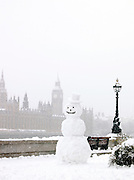 A snowman on the south bank of the River Thames opposite Big Ben and the Houses of Parliament, London, UK