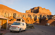 Sunrise illuminates our campervan in Goblin Valley State Park Campground, San Rafael Swell, in central Utah, USA. Admire fanciful hoodoos, mushroom shapes, and rock pinnacles in Goblin Valley State Park, in Emery County between the towns of Green River and Hanksville. The Goblin rocks eroded from Entrada Sandstone, which is comprised of alternating layers of sandstone (cross-bedded by former tides), siltstone, and shale debris which were eroded from former highlands and redeposited in beds on a former tidal flat. As part of the Colorado Plateau, the San Rafael Swell is a giant dome-shaped anticline of rock (160-175 million years old) that was pushed up during the Paleocene Laramide Orogeny 60-40 million years ago. Since then, infrequent but powerful flash floods have eroded the sedimentary rocks into valleys, canyons, gorges, mesas, and buttes.