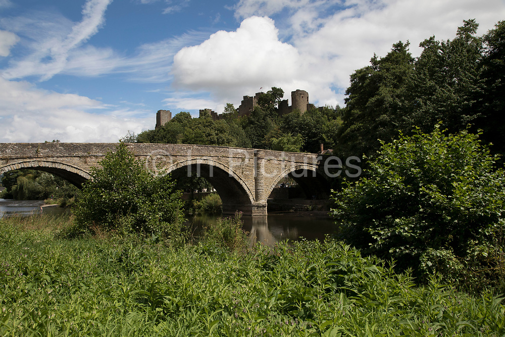 Bridge over the River Teme towards Ludlow Castle in Ludlow, United Kingdom. Ludlow is a market town in Shropshire, England. With a population of approximately 11,000, Ludlow is the largest town in south Shropshire. The town is near the confluence of two rivers. The oldest part is the medieval walled town, founded in the late 11th century after the Norman conquest of England. It is centred on a small hill which lies on the eastern bank of a bend of the River Teme. Atop this hill is Ludlow Castle and the parish church, St Laurences, the largest in the county. From there the streets slope downward to the River Teme.