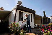 Lon Walker waters his garden at the Chateau Senior Mobile Home Park on Tuesday, Oct. 22, 2019, in Oroville, Calif. WalkerÕs wife, Ellen Walker, died in the 2018 Camp Fire at their Concow home.