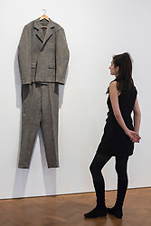 """© Licensed to London News Pictures. 17/04/2018. LONDON, UK. A staff member views """"Filzanzug (Felt Suit)"""", 1970, at the preview of """"Joseph Beuys: Utopia at the Stag Monuments"""", at the Galerie Thaddaeus Ropac in Dover Street.  The retrospective is the most important UK exhibition of Beuys' work in over a decade, presenting major sculptures and rarely seen works from 1947 to 1985, and runs from 18 April to 16 June.  Photo credit: Stephen Chung/LNP"""