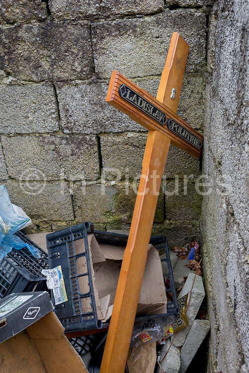 Discarded cross with a deceased persons name lying in a communal cemetery bin of a rural village in the Kozjansko Regional Park, on 24th June 2018, in Prevorje, Slovenia.