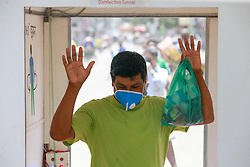 A man walks through a disinfection tunnel after its installation during the nationwide lockdown to curb the spread of coronavirus (COVID-19) at Mirpur, in Dhaka, Bangladesh. Artoonad, a social organization of the youth, has set up a disinfection tunnel as the country struggles to contain the spread of the novel coronavirus. Photo by Suvra Kanti Das/ABACAPRESS.COM