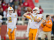 Nov 12, 2011; Fayetteville, AR, USA;  Tennessee Volunteers quarterbacks Matt Simms (12) looks on as Justin Worley (14) makes a pass before the start of a game against the Arkansas Razorbacks at Donald W. Reynolds Razorback Stadium. Arkansas defeated Tennessee 49-7. Mandatory Credit: Beth Hall-US PRESSWIRE
