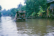 River traffic family houseboat passing wooden houses in rural area on waterway near Bankgkok, Thailand in 1964
