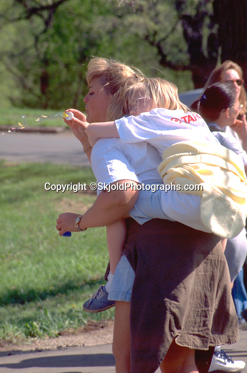 Mom with daughter on her back blowing bubbles age 26 and 7. AIDS Walk Minnehaha Falls Park Minneapolis Minnesota USA