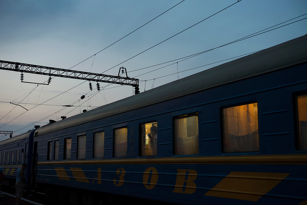 A female passenger on the 20-hour journey from Kiev to Mariupol looks out the window while drinking a cup of tea during a brief station stop two and a half hours out of Kiev.