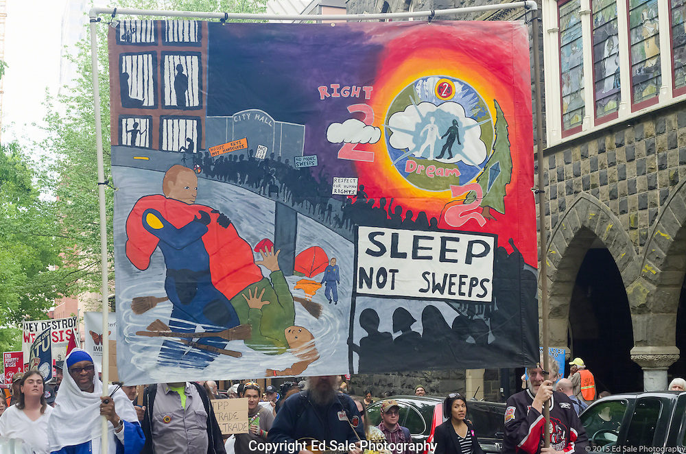 Demonstrator in 2015 May Day rally and march in Portland, Oregon hold large banner saying Sleep Not Sweeps which shows support the homeless