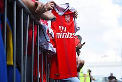 A fan holds an Arsenal shirt as the teams arrive