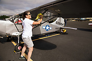 Aircraft Owner cleaning her L-5 at Warbirds Over the West.