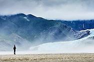 A man juxtaposed against the scenery of Mendenhall Glacier near Juneau, Alaska.