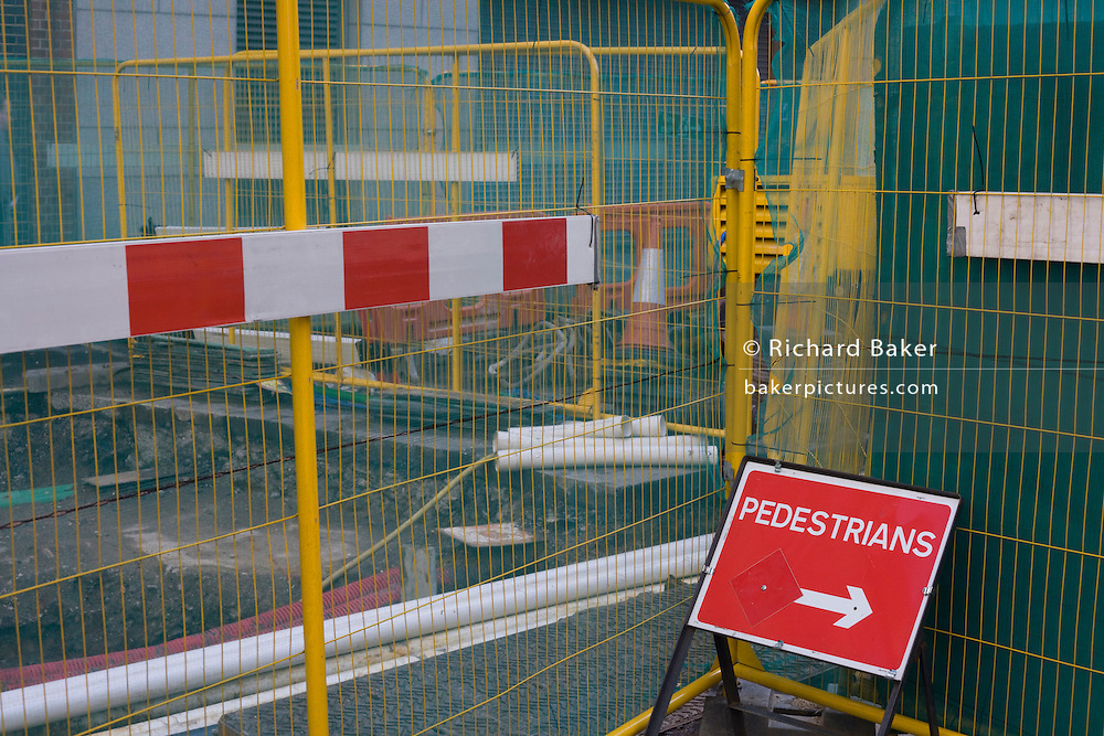 A pedestrian sign shows where to walk where roadworks have disrupted a street in Victoria where a regeneration project is underway.