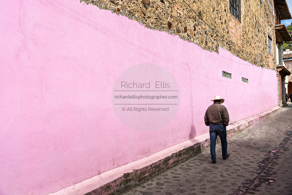 A cowboy walks past a bright pink building in Angangueo, Michoacan, Mexico. Angangueo is a tiny, remote mountain town and the entry point to the Sierra Chincua Monarch Butterfly Sanctuary.