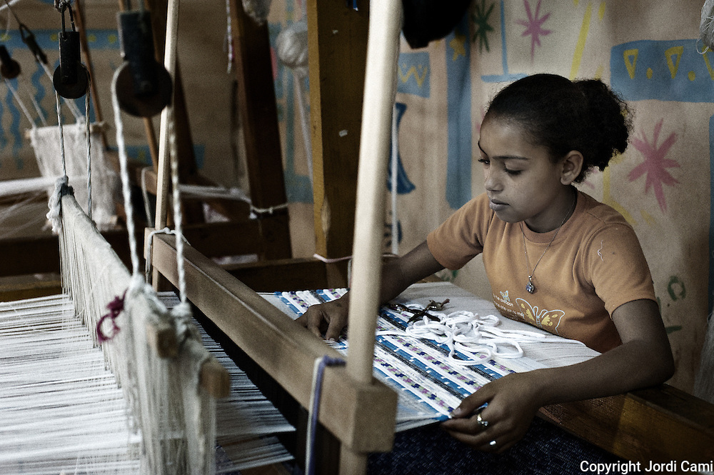 """A girl learns to weave carpets   in the workshop of the NGO, APE in Mokattam, using recycled scraps of clothing and textiles from factories throughout Egypt.On the outskirts of Cairo in the middle of Manshiet Nasr neighborhood is located Mokattam settlement known as """"Garbage City"""" is inhabited by Zabbaleen, a community of about 45,000 Coptic Christians living for decades to recycle waste generated by the Egyptian capital: plastic, aluminum, paper and organic waste transformed into compost. Most part of the Association for the Protection of the Environment (APE), an NGO that works in the area, whose objectives are to protect the environment and improve the livelihoods of garbage scavengers in Cairo. According to the UN, the work is done in Mokattam is one of the ten best examples of world environmental improvement. El Cairo , Egipt, June 2011. ( Photo by  Jordi Camí )."""