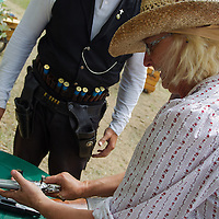 Participant unloads her weapon during the Cowboy Action Shooting European Championship in Dabas, Hungary on August 11, 2012. ATTILA VOLGYI