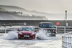 © Licensed to London News Pictures. 27/01/2019. Aberystwyth, UK. Cars drive through water on the promenade as gale force north-westerly winds blowing at up to 70mph drive waves into the promenade and sea walls at Aberystwyth in west Wales. A yellow Met Office warning for dangerously strong winds has been issued covering all of Wales and much of the wet of the UK. Photo credit: Keith Morris/LNP
