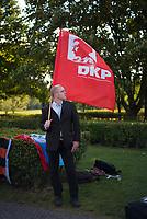 DEU, Deutschland, Germany, Berlin, 24.08.2015: Prorussische Demonstration vor dem Bundeskanzleramt gegen die Politik des ukrainischen Präsidenten Petro Poroschenko, der heute von der Bundeskanzlerin empfangen wird. Demonstrant mit der Fahne der Deutschen Kommunistischen Partei (DKP), Rosa Luxemburg.